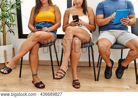 Group of hispanic people using smartphone and touchpad at waiting room.