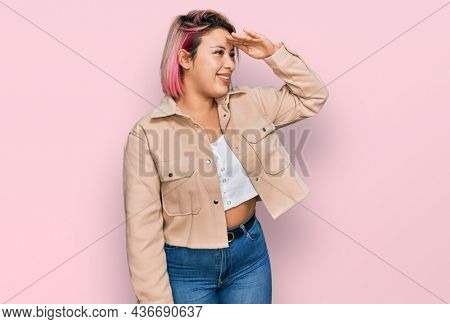 Hispanic woman with pink hair wearing casual clothes very happy and smiling looking far away with hand over head. searching concept.