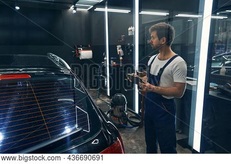 Worker Of Car Service Entering Information About Detailing To Tablet