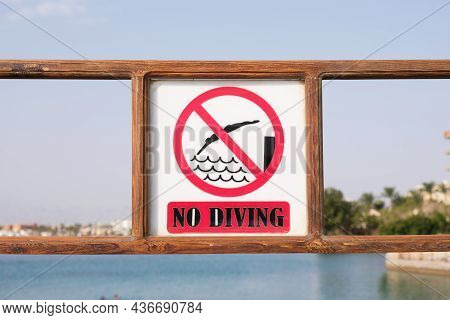 Sign No Diving On The Pier Of The Beach. A Prohibitory Sign Warning Of Danger When Diving Into The S