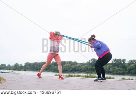 Wide Shot Of Overweight Young Woman Doing Squats Exercises Using Resistance Band For Weight Loss Wit