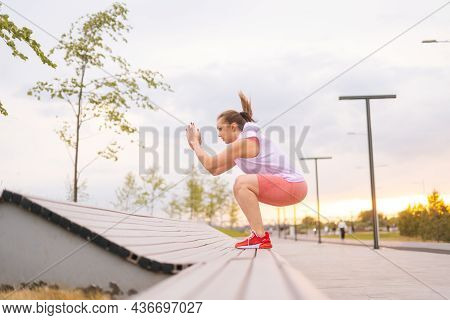 Side View Of Young Caucasian Fit Active Woman Jumping On Bench In City Park In Summer Morning. Muscu