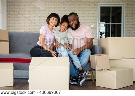 Mixed Race Families Are Sitting On The Sofa For Rest After Moving To A New House On The First Day Af