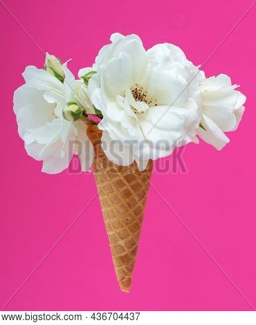 Ice cream waffle cone with a bouquet of summer flowers white roses over pink background. Diet and thinking outside the box design concept