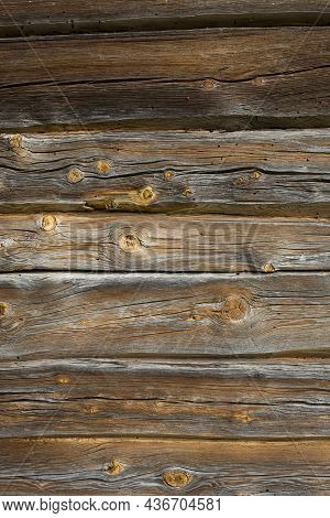Wooden Logs Of An Old House. Close-up. Weathered Natural Gray Wood Texture. Background. Vertical Pho