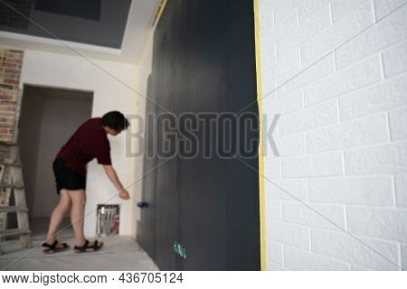 Roller Wall Painting. Man standing near black wall and holding roller, back view. Worker paints wall, home renivation. Painter at work. Home renovation