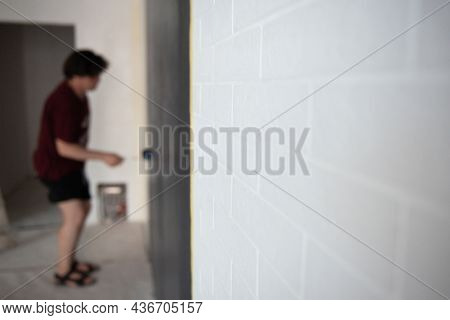 Roller Wall Painting. Worker paints wall, home renivation, focus is on the  white bricks. Painter at work. Home renovation