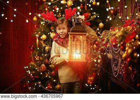 Portrait of a happy cheerful boy holding a lantern in his hands against the background of a festively decorated Christmas tree. Merry Christmas and Happy New Year!