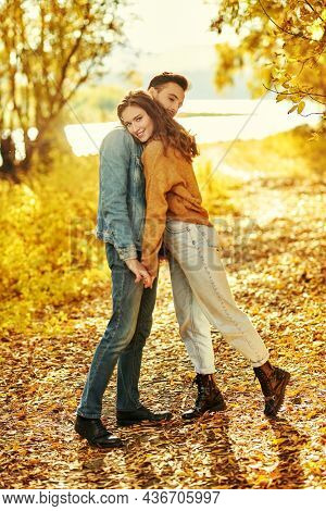Sweet young people in love enjoy a wonderful autumn day walking together by the river. Full length portrait. Love and relationship.
