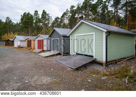 Colorful Wooden Houses To Keep The Boats In On The Lake Shore. Stora Sjofallet National Park, Sweden