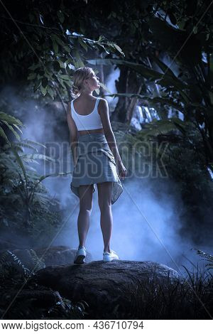 Portrait Of Nice Young Woman Is Walking  In The Jungle At Midnight