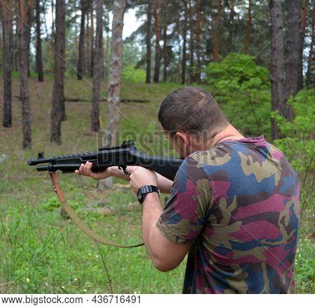 Man with Turkish 12-gauge rifle Hatsan Escort MP(pump action shotgun). Unformal shooting range near Kiev. May 26, 2021. Kiev Region, Ukraine