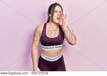 Young hispanic girl wearing sportswear shouting and screaming loud to side with hand on mouth. communication concept.