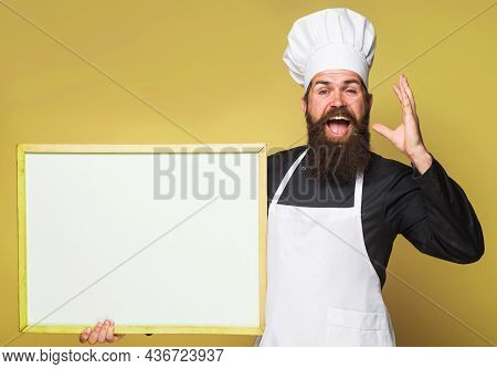 Chef Man With Empty Menu. Cook With Blank Chalkboard With Copy Space For Text. Bearded Baker With Ad