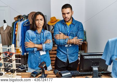 Young interracial people working at retail boutique skeptic and nervous, disapproving expression on face with crossed arms. negative person.