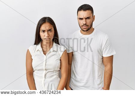 Young interracial couple standing together in love over isolated background skeptic and nervous, frowning upset because of problem. negative person.