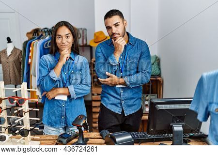 Young interracial people working at retail boutique looking confident at the camera with smile with crossed arms and hand raised on chin. thinking positive.