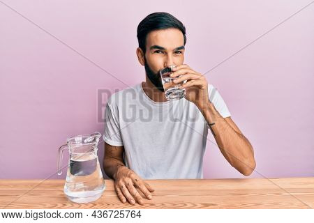Hispanic man with beard drinking a glass of fresh mineral water sitting on the table