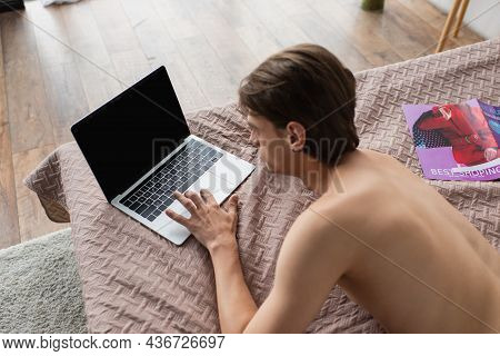 High Angle View Of Shirtless Transgender Young Man Using Laptop With Blank Screen On Bed