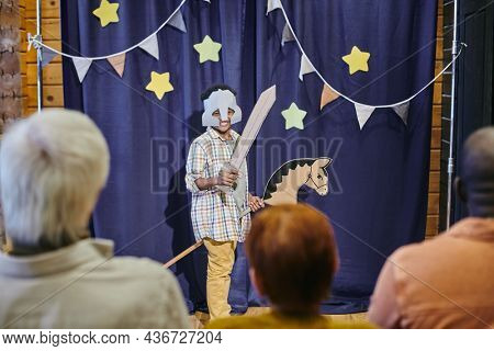 Boy in stage costume acting on the scene, he showing the performance to people