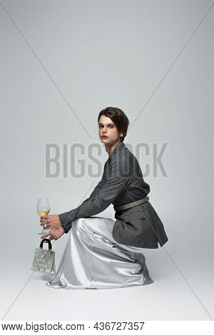 Full Length Of Transgender Man In Slip Dress With Blazer Holding Purse And Glass Of Wine While Sitti