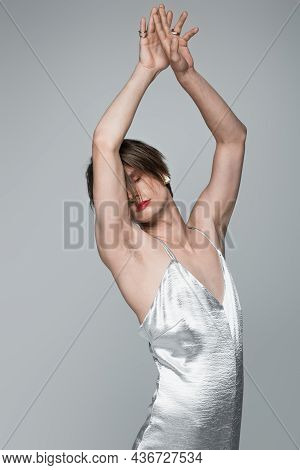 Young Transgender Man With Red Lips And Earring Posing With Raised Hands Isolated On Gray