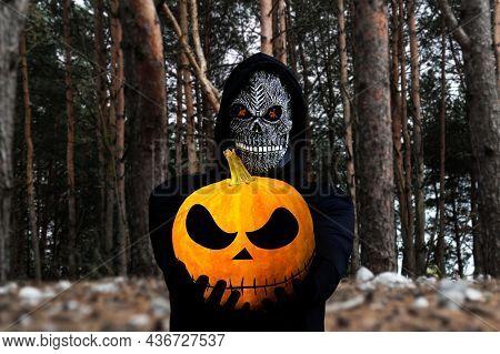 Grim Reaper Holding Halloween Pumpkin Head. Man In Death Mask With Fire Flame In Eyes On Dark Black