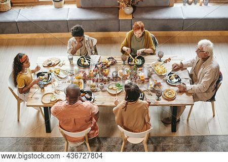 High angle view of big family sitting at dining table and having dinner together