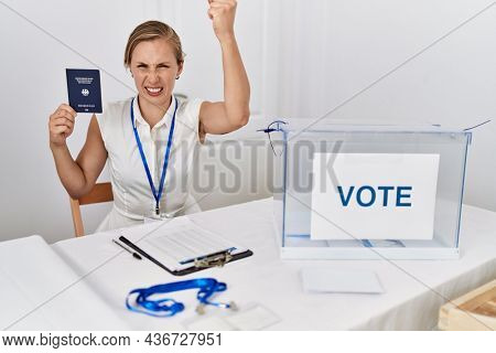 Young blonde woman at political campaign election holding germany passport annoyed and frustrated shouting with anger, yelling crazy with anger and hand raised