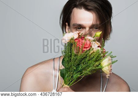 Young Transgender Man Holding Flowers While Covering Face Isolated On Gray