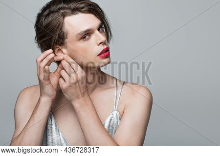 Young Transgender Man Touching Ear Isolated On Grey