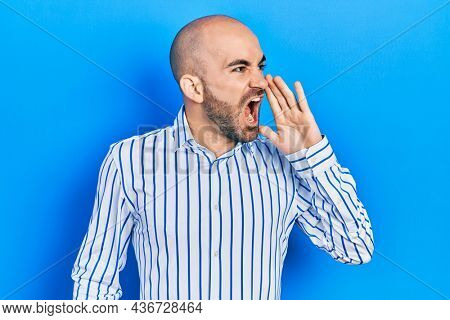 Young bald man wearing elegant clothes shouting and screaming loud to side with hand on mouth. communication concept.