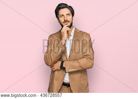 Young hispanic man wearing business clothes with hand on chin thinking about question, pensive expression. smiling and thoughtful face. doubt concept.