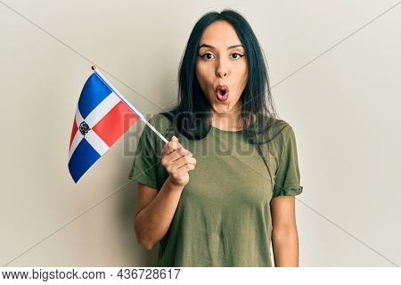 Young hispanic girl holding dominican republic flag scared and amazed with open mouth for surprise, disbelief face
