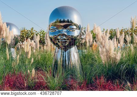 Krasnodar, Russia - October 18, 2021:large Baby Heads With Smiling Faces In Mirrored Metal.