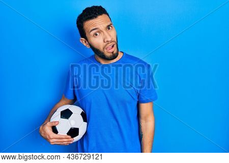 Hispanic man with beard holding soccer ball in shock face, looking skeptical and sarcastic, surprised with open mouth