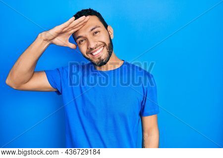 Hispanic man with beard wearing casual blue t shirt very happy and smiling looking far away with hand over head. searching concept.