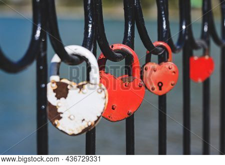 A Red Love Lock Attached To The Railing Of The Bridge.