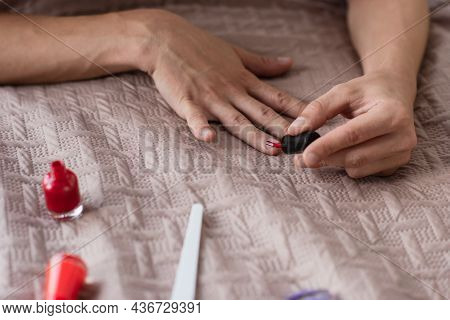 Cropped View Of Transgender Young Man Doing Manicure In Bedroom