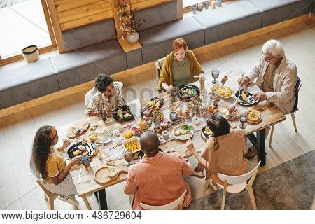 High angle view of family sitting at dining table and having dinner together in the room