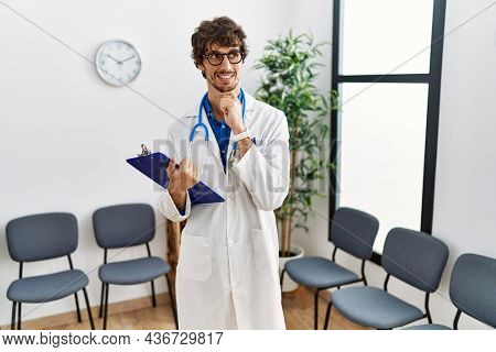 Young hispanic doctor man at waiting room with hand on chin thinking about question, pensive expression. smiling and thoughtful face. doubt concept.