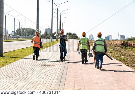 Workers In Helmets And Overalls With Shovels Go To The Work Facility. Work In An Urban Environment.