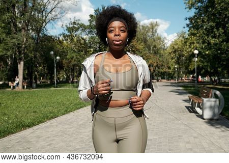 Young plus size sportswoman with earphones jogging in park on sunny morning