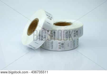 Skein Tags For Clothing, Satin Ribbon With Symbols For The Use Of Clothing. White Skeins, A Roll Of