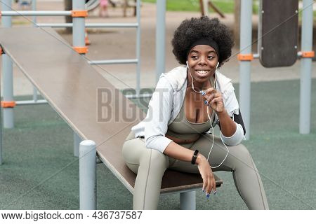 Young smiling sportswoman with earphones communicating through mobile technologies while sitting on sportsground