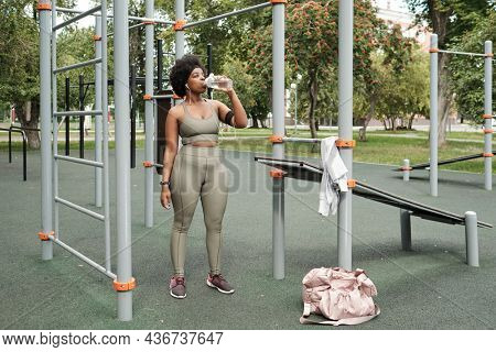Young sportswoman standing on sportsground and having water during break after workout