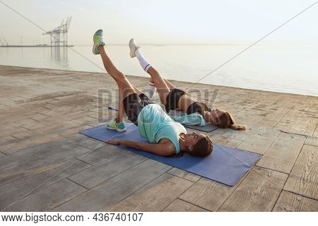 Young fit girls on fitness mats doing workout. Sporty caucasian females in sportswear exercising on wooden platform at sunrise. Two girlfriends doing sport on sunny day