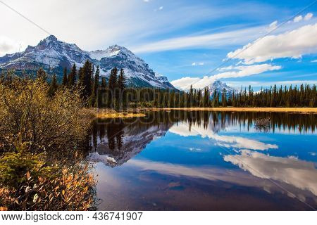 The mountains, forests and lakes in the Rockies of Canada. Clouds reflected in the smooth water of the lake. Autumn trip to the Rockies of Canada. The concept of active, eco and photo tourism