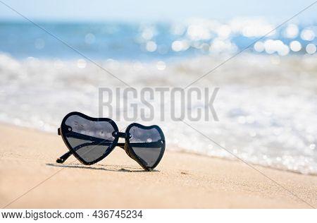 Sunglasses On The Beach Near The Sea Waves. Selective Focus, Narrow Focus.