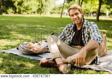 White man smiling while his son sleeping in baby carriage at green park